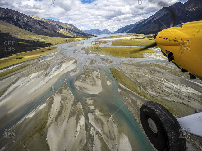 Propeller and wheel of a plane flying over wetlands at Lake Hawea, New Zealand