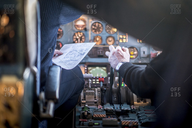 Two pilots and controls in the cockpit of an airplane