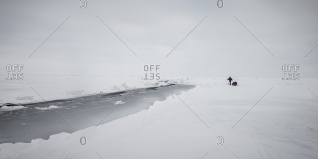 Explorer walking across an ice field near an Arctic river