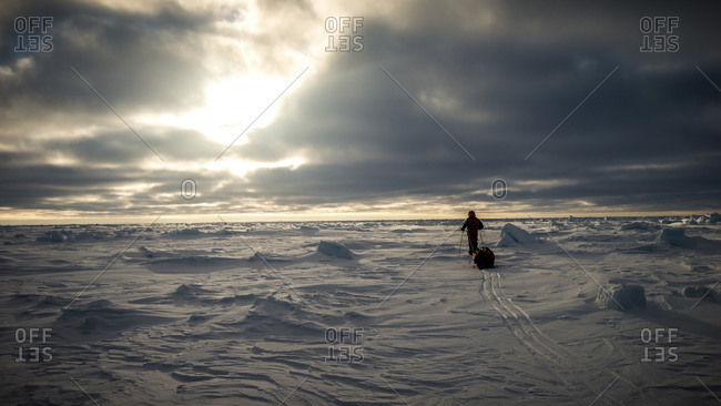 Person pulling a sled of supplies across a frozen Arctic ice field
