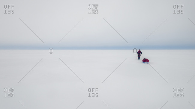 Explorer pulling her gear across a vast ice field in the Arctic