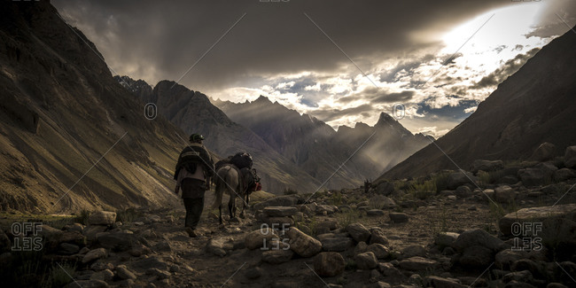 Explorer and horse traveling through the mountains of Pakistan