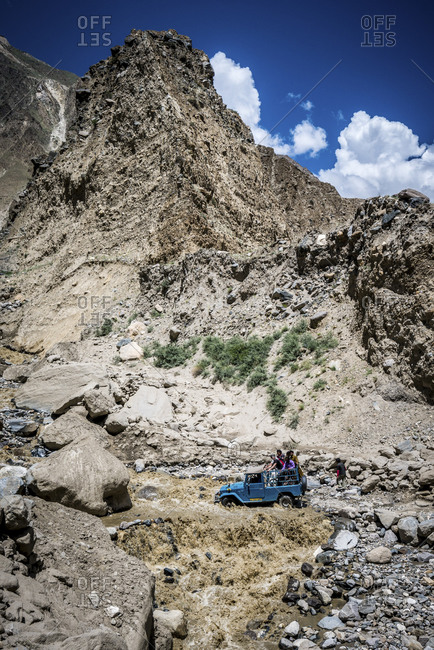Group of people riding through muddy waters in an SUV in the mountains of Pakistan