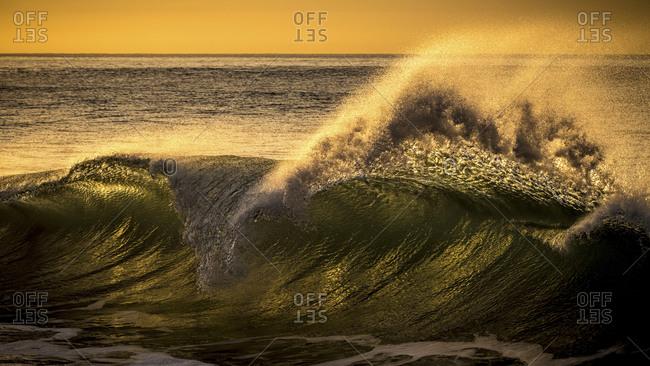 Ocean wave crashing at sunset