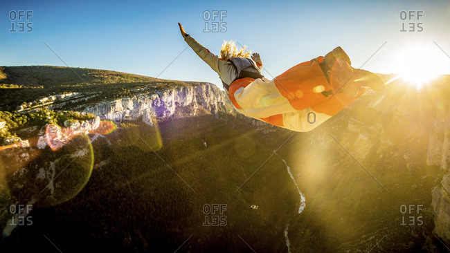 Man in mid-air during a BASE jump from a mountain cliff