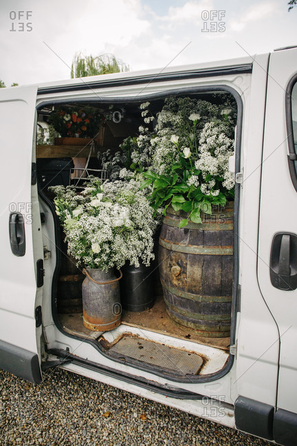 Flowers in a delivery van being delivered in preparation for a wedding ceremony and reception