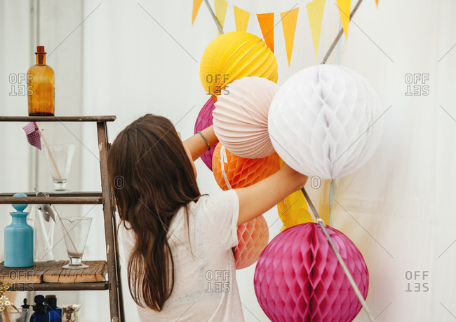 Woman arranging Chinese paper lantern balloons on a wall