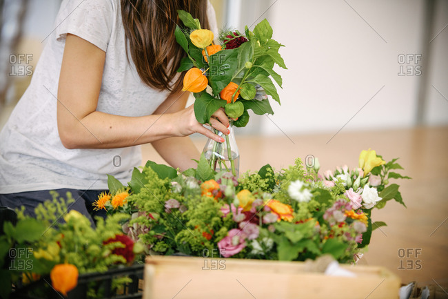 Woman inspecting freshly delivered flowers for a wedding ceremony