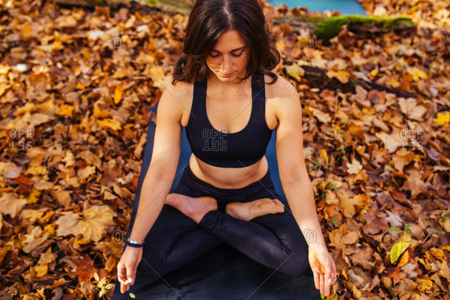 Elevated view of woman in lotus pose on mat in autumn woods