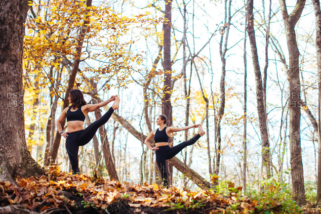 Women balancing in yoga position in woods