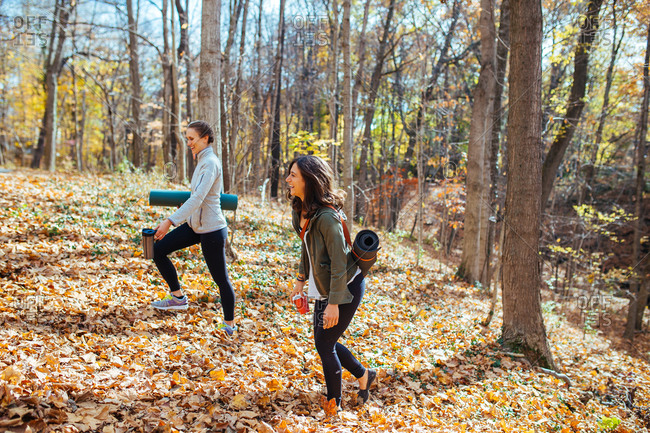 Women carrying their yoga mats in autumn woods for workout