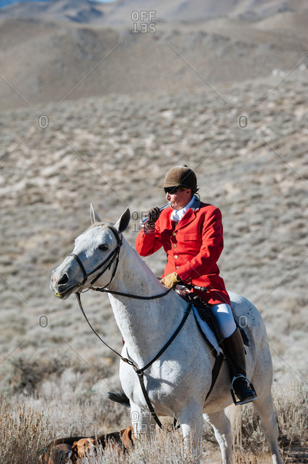 Nevada, USA - October 8, 2014: Huntsman in traditional red jacket blows a horn to signal participants