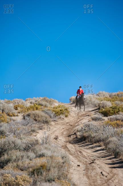 Nevada, USA - October 8, 2014: Rider in red coat on horseback on desert trail