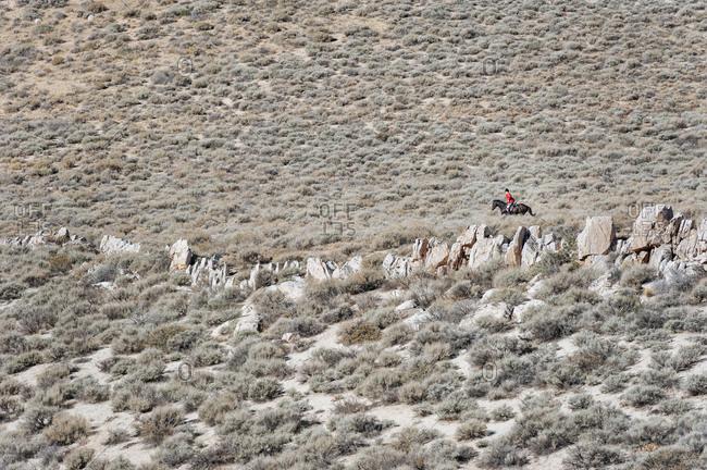 Horse rider in desert brush along a rock ridge