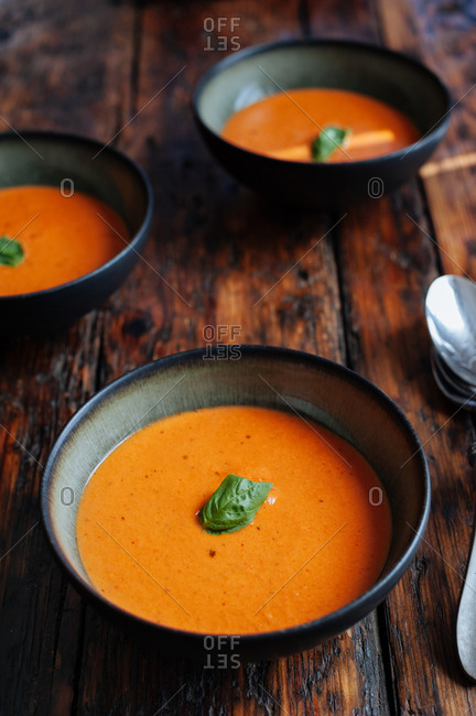 Bowls of tomato bisque with basil on wooden table