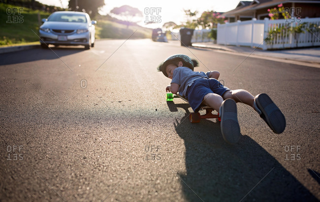 Boy lying flat on a skateboard rolling down a street