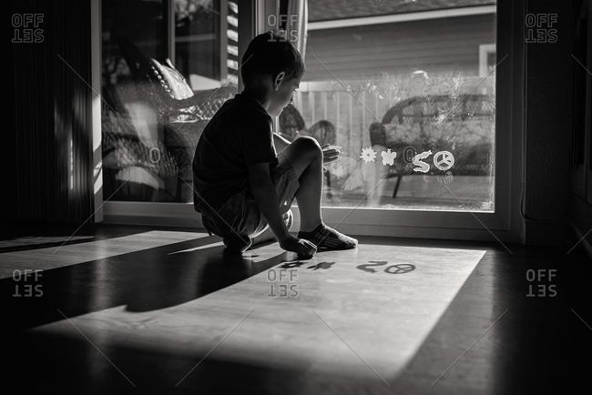 Boy putting sticky gel clings on a window