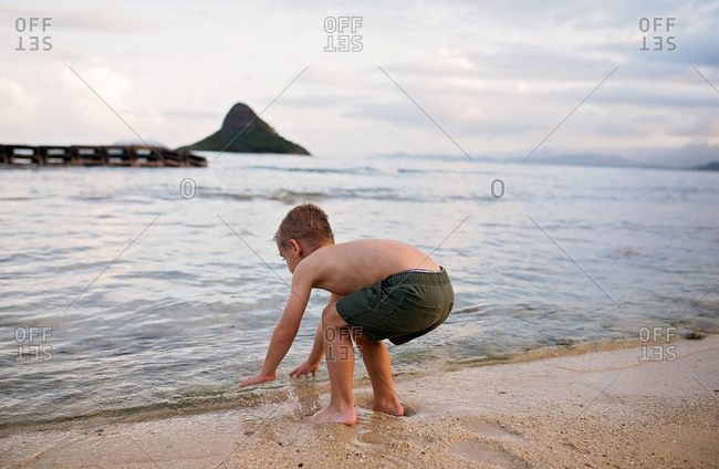 Boy crouching on the beach at the water's edge