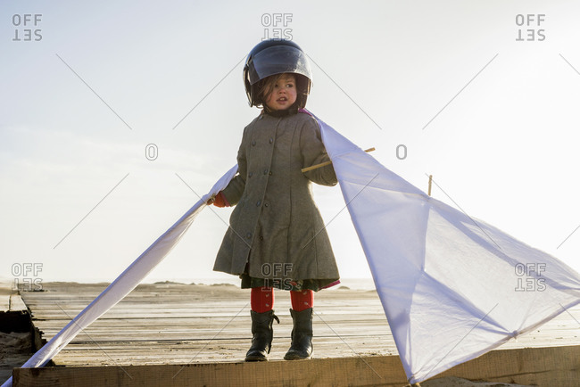Young girl in helmet holding kite wings on beach at sunset