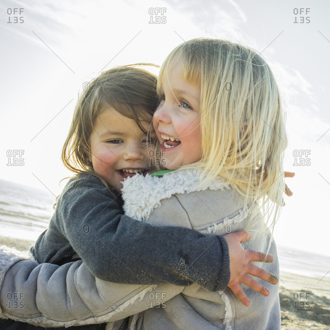 Two little girls hug each other on beach