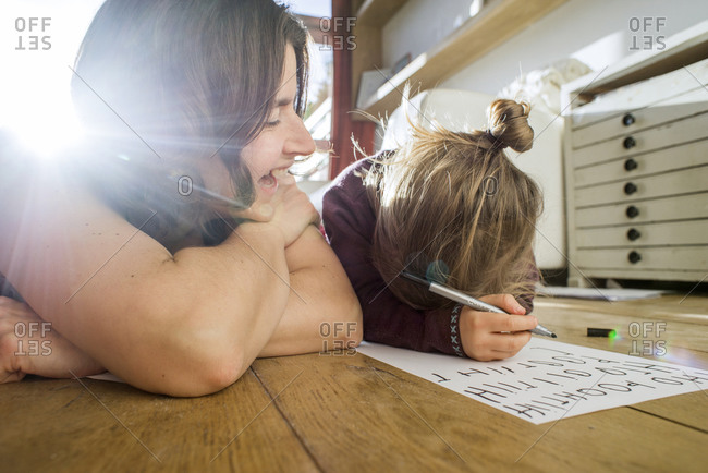 Toddler girl practicing writing on floor with mother