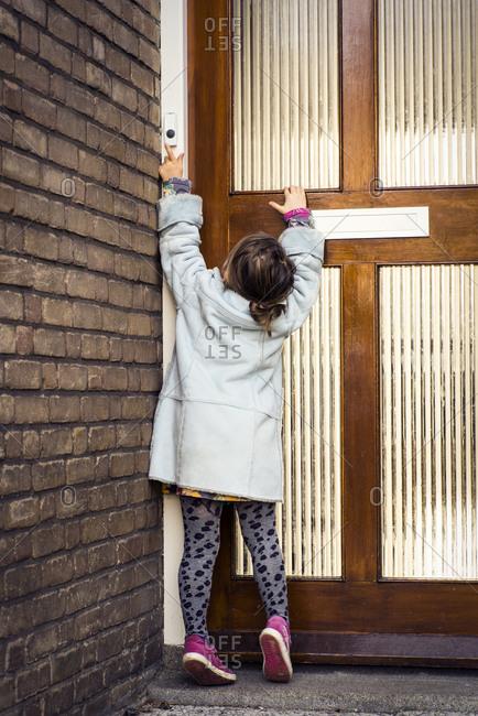 Little girl stands on tiptoe at door to ring doorbell