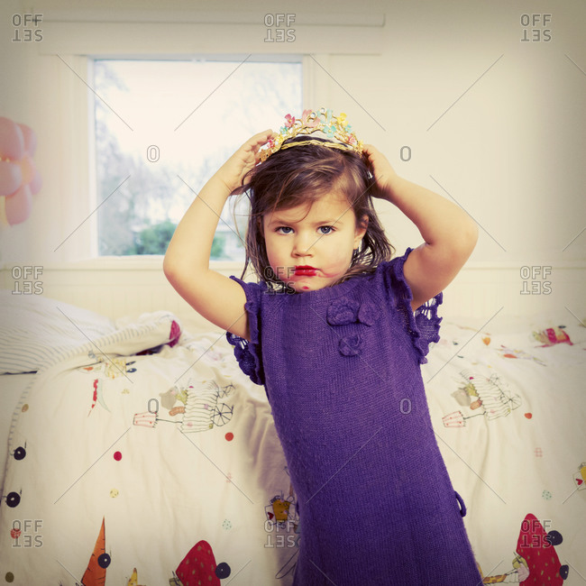 Young girl with smeared lipstick playing with toy crown