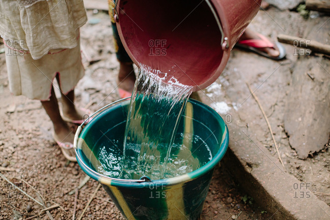 Water being poured from one bucket to another