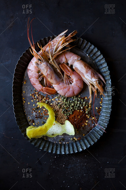 Overhead view of whole fresh prawns on plate with spices and lemon rind