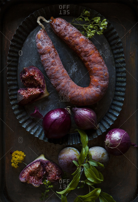 Overhead view of platter of chorizo sausage, red onions, and figs