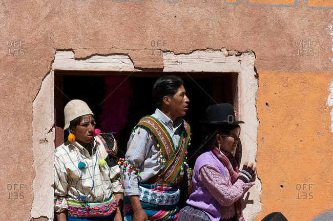 Macha, Bolivia - May 5, 2010: Villagers watch from a doorway as rival villages fight in the streets of Macha during the Tinku Festival in Macha, Bolivia