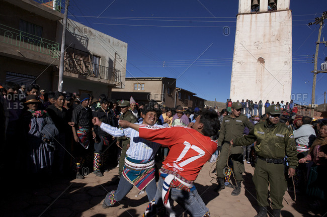 Macha, Bolivia - May 4, 2010: Police watch over one-on-one fighting between rival villagers in the streets of Macha during the Tinku Festival in Macha, Bolivia
