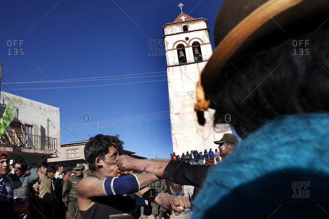 Macha, Bolivia - May 4, 2010: One-on-one fighting between rival villagers in the streets of Macha during the Tinku Festival in Macha, Bolivia