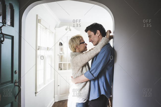 Couple standing in a doorway with arms around one another