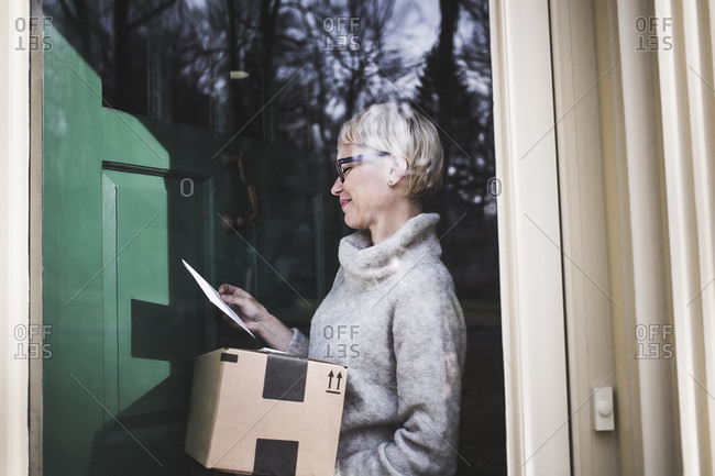 Woman standing at front collecting mail and a package