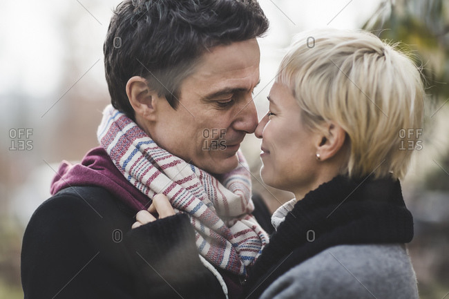 Couple in scarves standing nose to nose