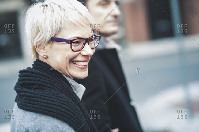 Close up of couple walking down a city street arm in arm