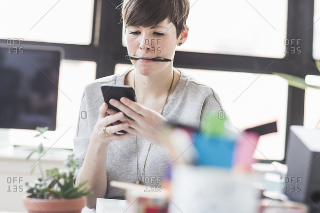 Woman texting on a smart phone with a pen in her mouth
