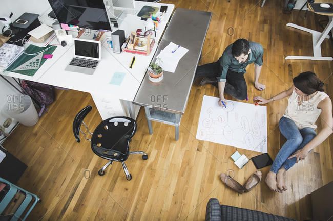 Colleagues brainstorming on the floor of a casual office