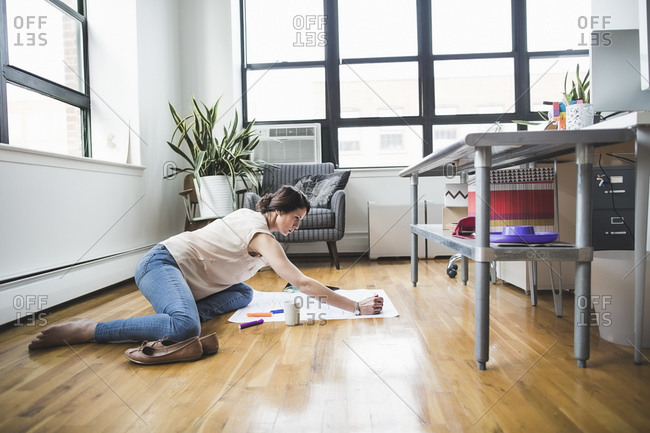 Woman brainstorming on the floor of a casual office