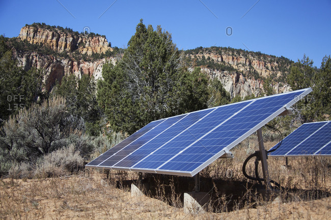 Solar panels in remote field near mountains,