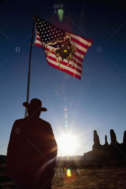 Man holding United States flag with Native American depiction near rock formations