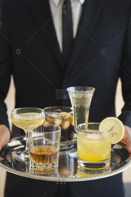 Close up of  waiter holding tray of drinks of yellow drinks