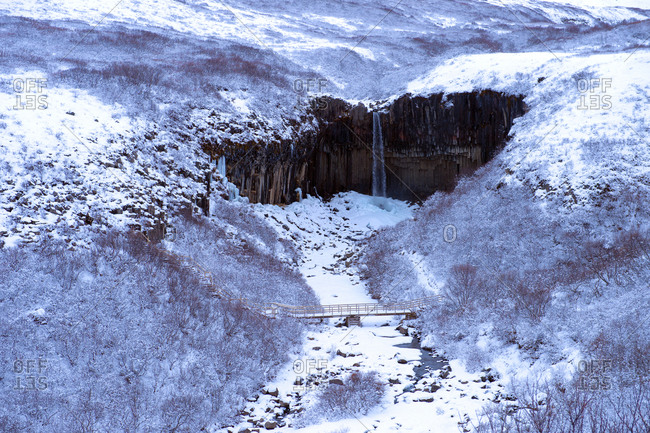 Waterfall and river in snowy landscape, Svartifoss, Sudhurland, Iceland