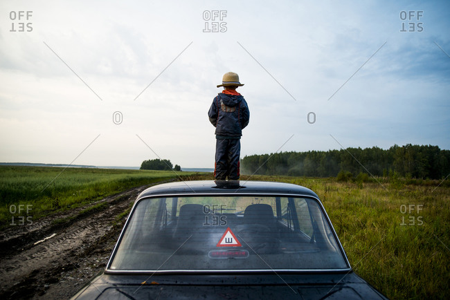 Boy standing on car roof in rural field