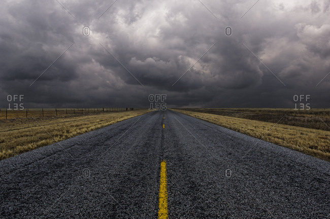 Paved road under cloudy sky in remote landscape