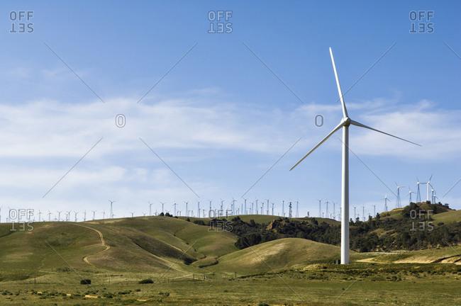 Wind turbines lining hilltop in rolling landscape