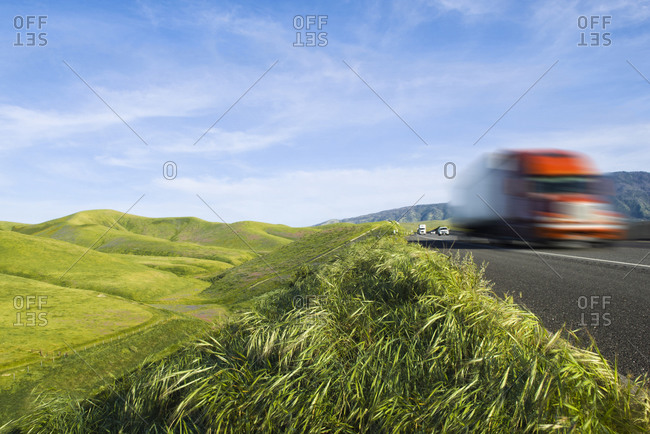 Truck driving on remote highway in rolling landscape