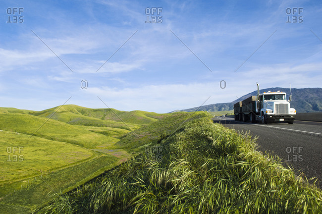 Truck driving on remote road in rolling landscape