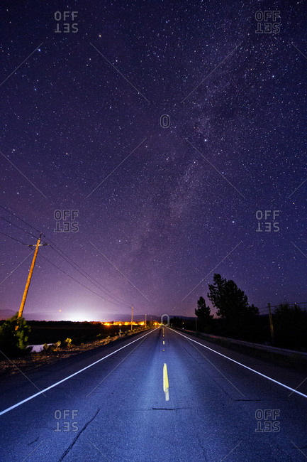 Paved road under starry night sky illuminated by headlights